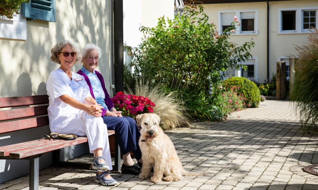 Zwei ältere Damen sitzen draußen auf einer Bank mit Hund