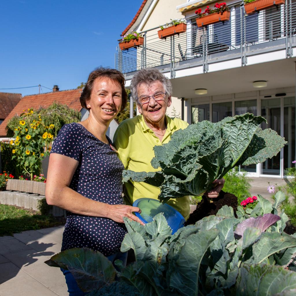 Ältere Dame und Frau im Garten